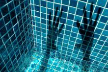 Full Frame Shot Of Hand Shadows Against Blue Mosaic Wall