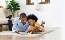 African American Father And His Son Lying Reading Book On The Floor