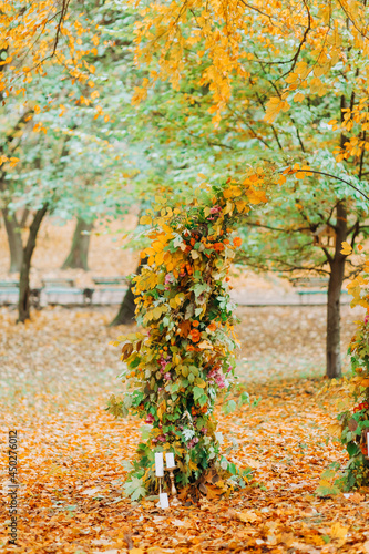 Wedding arch with leaves and flowers in the autumn park.