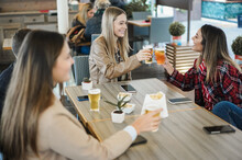 Young Friends Having Fun Clinking With Beer Inside Bar Restaurant - Focus On Center Girl Face
