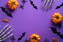 Halloween Decorations On Purple Background. Happy Halloween Concept. Flat Lay Pumpkins, Bony Hands, Bats Silhouettes, Spiders.