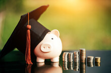 Piggy Bank With Graduation Cap On Black Glass Floor,Money Saving Concept..