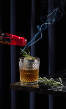 Smoked Whiskey Cocktail With Smoking Lavender Rosemary On Black Granite Bar Table Top With Dark Curtain Background.  Whiskey Bottle Is Pouring  Into The Drink. Large Square Ice Cube