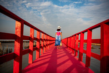 Young Woman Walking On The Red Boardwalk Over The Marshland.