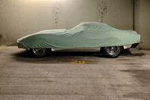 Sports Car Under A Protective Cover In A Garage