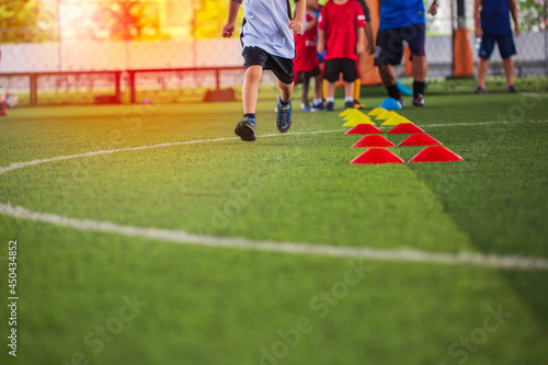 Soccer ball tactics on grass field with barrier for training children jump skill