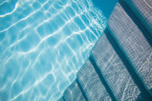 Edge Of Blue Swimming Pool. Summer Water Sport, Recreational Background. Texture Of Water Surface, Blue Turquoise Vivid Bright Sunny Closeup With Stairs Into The Pool. Relax Vacation Abstract Concept