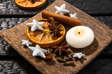 Winter Relaxing Aromatherapy. Side View Of Various Spices: Cinnamon Stick, Clove, Star Anise, Dried Orange Slices. Wood Tray With Seasonal Potpourri On Effect Black Burnt Wood Background.