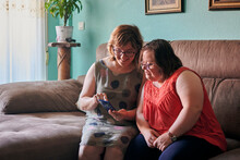 Adult Woman And Her Sister With Down Syndrome Look At A Phone At Home