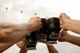 Fototapeta Kawa jest smaczna - Friends clinking glasses with beer in outdoor cafe, closeup