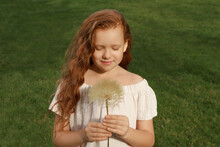 Cute Girl With Beautiful Red Hair Holding Large Dandelion In Park. Allergy Free Concept