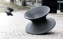 Large Grey Spinner Sculpture Outside Building