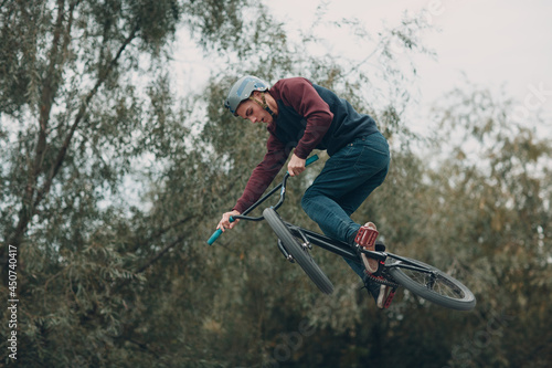 Professional young sportsman cyclist with bmx bike at skatepark