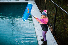 5 Years Old Girl Cleaning The Swimming Pool During Fall