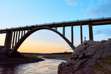 Stone Bridge Over River With A Sunset Sky With A Woman Climbing