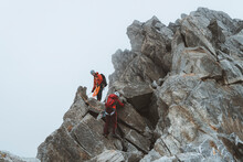 Two Climbers Descending Exposed Ridge On Icy Day
