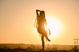Beautiful fit girl exercise, dancing in transparent tunic and warm sun light with water and warm sky view