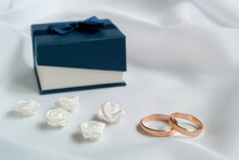 Gold Wedding Rings, White Artificial Flowers To Decorate The Hairstyle And Blue Jewelry Box On White Fabric.