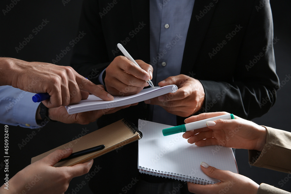 Man signing autograph in notebooks on dark background, closeup