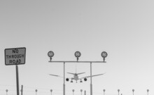 Jet Aircraft On Final Approach Over Navigation Lights At The End Of The Runway At An International Airport - Black And White