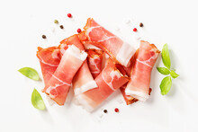 Tasty Prosciutto Slices With Basil Leaves And Spices On White Background