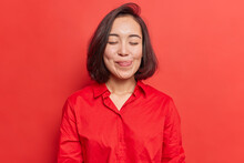 Pretty Brunette Young Asian Woman Closes Eyes Licks Lipsfrom Temptation To Taste Something Delicious Shows Tongue Imagines Eating Delicious Food Wears Shirt Isolated Over Vivid Red Background