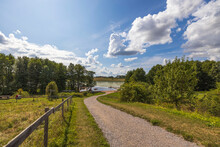 Gorgeous Views Of The Natural Landscape. Country Road To Lake Between Green Trees On A Blue Sky With A Background Of White Clouds.  Sweden.