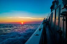 夕陽に向かって出船するフィッシングボート