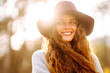 Stylish woman in sweater and hat enjoys autumn nature. People, freedom, lifestyle, travel and vacations concept.