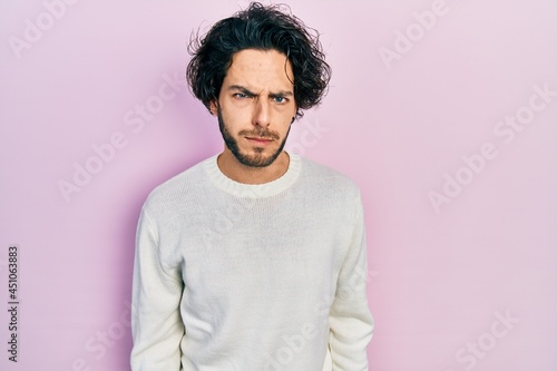 Stampa su Tela Handsome hispanic man wearing casual white sweater skeptic and nervous, frowning upset because of problem