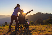 Disabled Handicapped Young Man In Wheelchair Walking With His Care Helper In Sunset.Silhouette