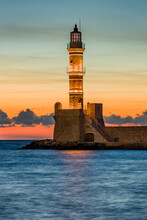 Ancient Venetian Lighthouse Guarding The Old Port Of Chania, Greece At Sunset
