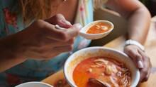 Pretty Woman Eating Thai Tom Yam Soup In A Restaurant