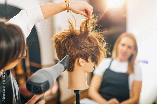 Hairdresser with the Hair Dryer in Hands Teaching Students How to do Hairstyling