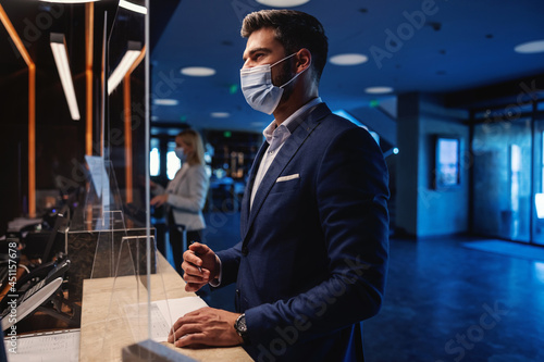 Businessman with face mask standing at reception and checking in to the hotel during coronavirus pandemic. Business trip, travel destinations, COVID-19 outbreak situation