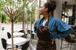 Leinwandbild Motiv Black waitress wearing apron standing while working in cafe outdoors