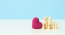 Red Knitted Heart And Wooden Figurines Family On A Blue Background. The Concept Of Cohesion And Love In The Family, Love For Children