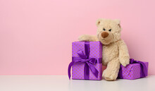 Cute Brown Teddy Bear Holding A Box Wrapped In Paper And Red Silk Ribbon On White Table. Prize And Congratulations, Pink Background