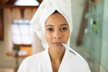 Portrait Of Mixed Race Woman In Bathroom Holding Toothbrush In Mouth Looking At Camera