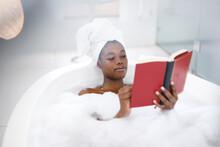 Happy African American Woman In Bathroom Relaxing In Bath Reading Book