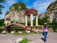 """Happy Asian Woman In Colorful Vest Standing At Public Rock Mountain Park At Ratchaburi, Thailand, Letter On Bridge Label Is """"Khao Hin Ngu (snake Stone) National Park"""""""