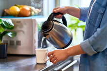 Female Hands Pouring Boiling Water From A Modern Metal Stainless Kettle In A Glass Cup For Brewing Tea In The Kitchen At Home