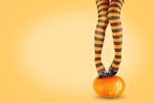 Women's Legs In Striped Stockings On A Pumpkin.