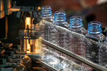 Abstract Scene Plastic Bottle Blowing Machine And Empty PET Bottles  On The Conveyor Belt.