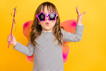 Photo of cool little blond hair girl hold stick wear wings spectacles wand striped shirt isolated on yellow color backgound
