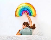 Woman With Rainbow Balloon Sleeping In Bed