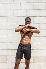 Muscular Black Sportsman Putting On Tank Top In Street