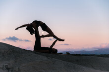 Flexible Couple Practicing Acro Yoga In Sunset
