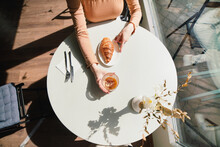 Anonymous Woman With Coffee And Croissant At Table In Cafe