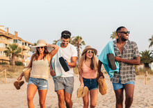 Company Of Happy Multiracial Friends Walking On Seashore In Summer
